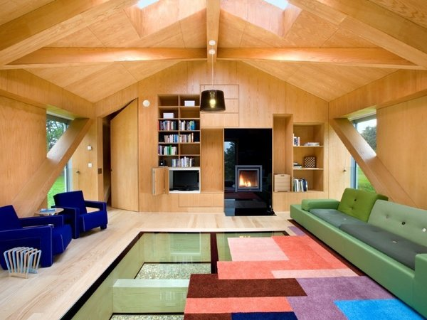 Living Room, Pendant Lighting, Wood Burning Fireplace, Sofa, and Light Hardwood Floor  Photo 5 of 11 in Take a Modern British Holiday in a Gleaming Cantilevered Barn