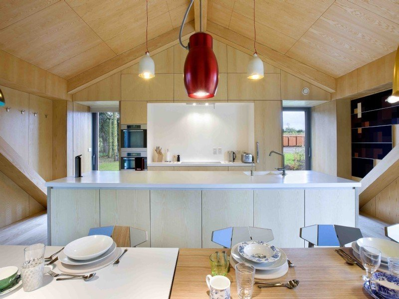 Kitchen, Pendant Lighting, Engineered Quartz Counter, Microwave, Wall Oven, and Undermount Sink  Photo 6 of 11 in Take a Modern British Holiday in a Gleaming Cantilevered Barn