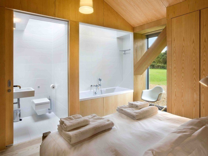 Bath Room, Alcove Tub, Ceramic Tile Floor, One Piece Toilet, Ceramic Tile Wall, Wall Mount Sink, and Soaking Tub  Photo 8 of 11 in Take a Modern British Holiday in a Gleaming Cantilevered Barn