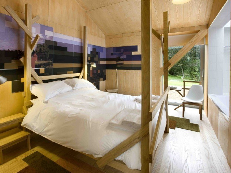 Bedroom, Bed, Chair, and Light Hardwood Floor  Photo 9 of 11 in Take a Modern British Holiday in a Gleaming Cantilevered Barn