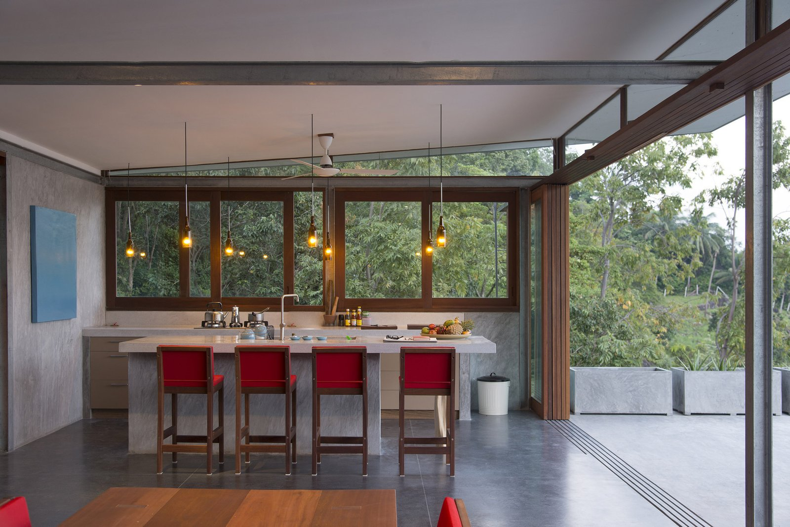 Trees, Bookcase, Sofa, Metal Fences, Wall, Chair, Kitchen, Side Yard, Concrete Floor, Range, Pendant Lighting, and Stone Counter  Photo 7 of 11 in Take a Trip to This Photographer-Designed Concrete Home in Thailand