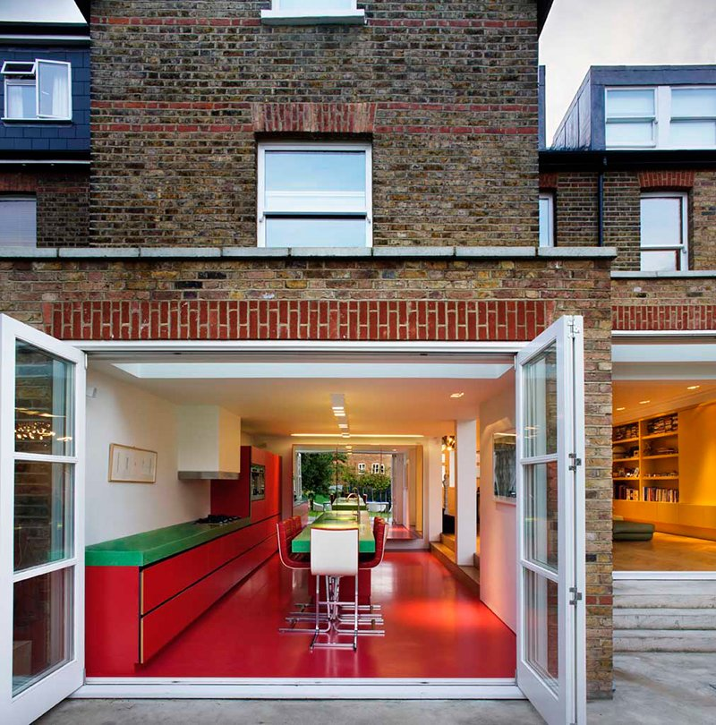 London architecture studio AMA remodeled this home in an old Edwardian building with bold Bauhaus colors, and transformed the kitchen into an audacious red and green space with glossy vermillion floors. Tagged: Kitchen, Wall Oven, Range Hood, Range, Ceiling Lighting, Recessed Lighting, and Colorful Cabinet.  Photo 2 of 13 in Bright Bauhaus Colors Fill This Brick Edwardian House in London