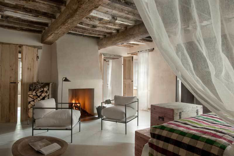 Bedroom, Bed, Concrete Floor, Chair, and Floor Lighting  Photo 3 of 10 in Rustic Meets Modern In This Tuscan Village Boutique Hotel
