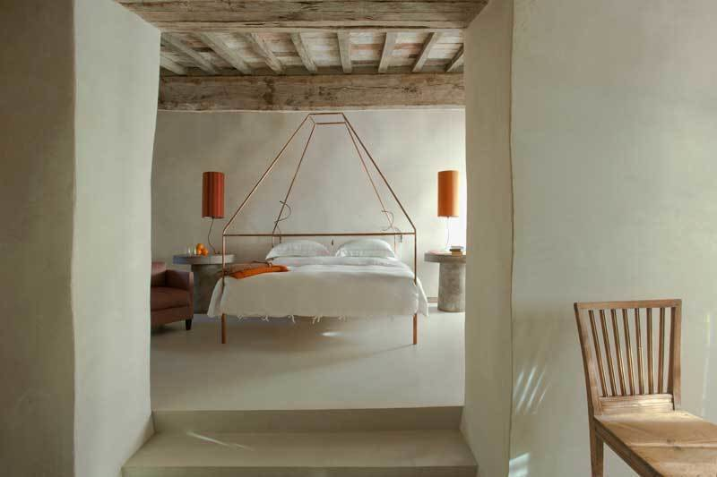 Bedroom, Bed, Night Stands, Chair, Table Lighting, and Concrete Floor  Best Photos from Rustic Meets Modern In This Tuscan Village Boutique Hotel