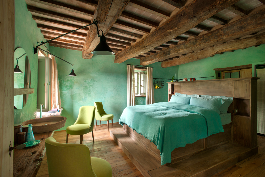 Bedroom, Wall Lighting, Chair, Bed, and Medium Hardwood Floor  Photo 10 of 10 in Rustic Meets Modern In This Tuscan Village Boutique Hotel