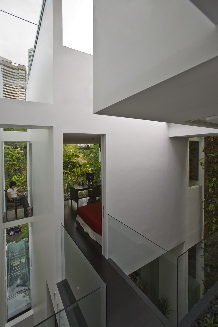 Dark Hardwood Floor, Metal Tread, Sofa, Wood Patio, Porch, Deck, Ceiling Lighting, Table, Rooftop, Gardens, and Hallway  Photo 9 of 13 in This Modern Home in Singapore Is a Living Urban Jungle