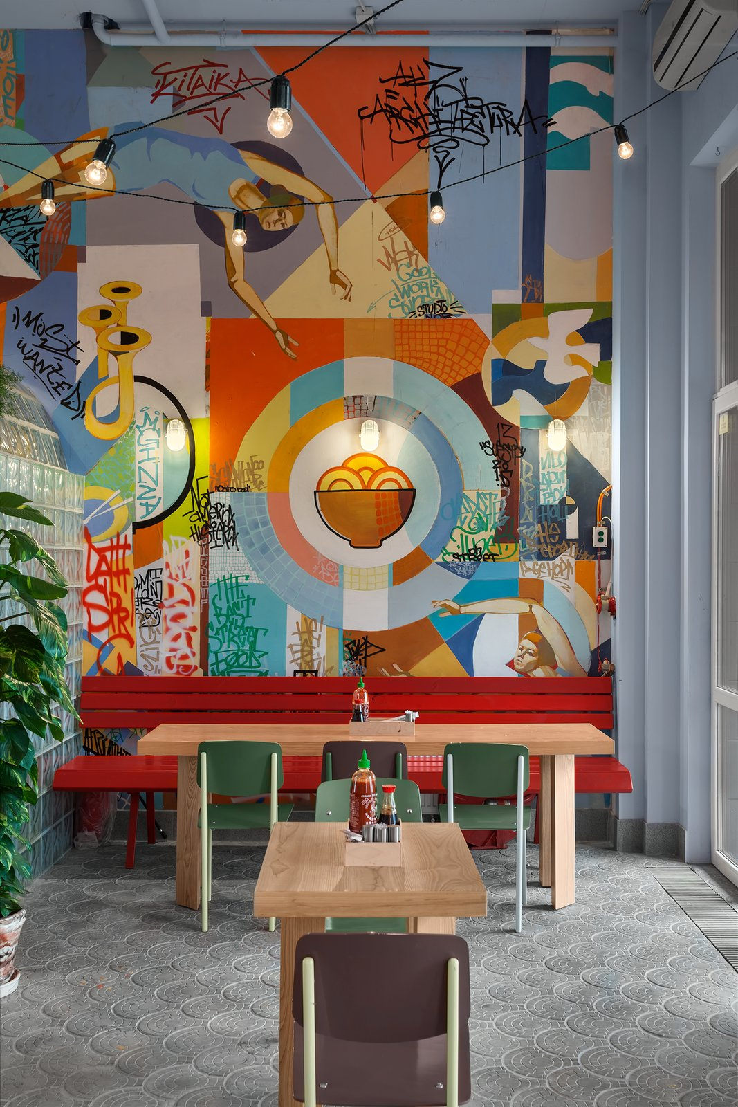 A vibrant and eclectic 65-seater diner in Kiev, Ukraine that serves Asian street food, Kitaika designed by AKZ Architectura was inspired by street culture in Asia and Ukraine. Combining carnival-like elements, bold colors, garlands of exposed light bulbs, and eye-catching graffiti, this little diner is a surreal and delightful take on Asian dining.  Photo 4 of 12 in 5 Interesting and Surprising Asian Eateries Around the World