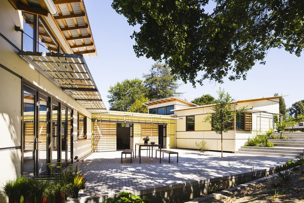 On a north-sloping site in Palo Alto, California, the three distinct volumes are jointed in this residence to create an internally focused private courtyard adjacent to a mature stand of live oak trees.  Photo 2 of 10 in 10 Homes With Large, Well-Ventilated Courtyards