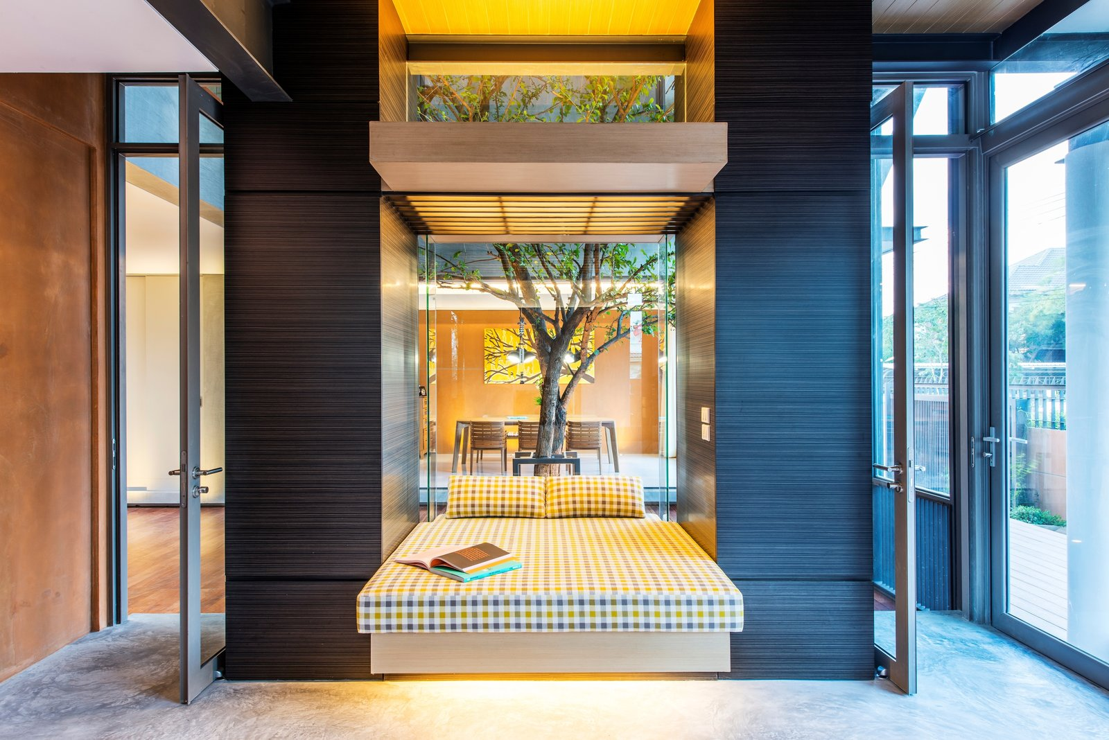 Inspired by the communal terrace courtyards of traditional multi-generational Thai homes, Thai architectural practice TA-CHA Design positioned a courtyard with a large tree in the center of the house to encourage good circulation and increase interaction between household members.  Photo 10 of 10 in 10 Homes With Large, Well-Ventilated Courtyards