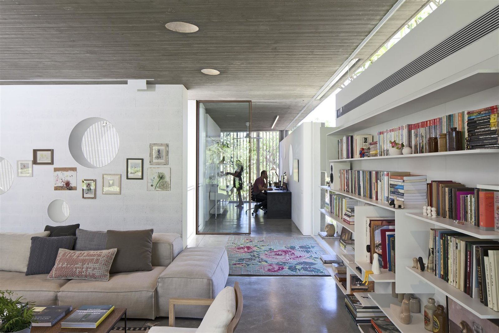 Tagged: Living Room, Sofa, Bookcase, Concrete Floor, Rug Floor, Shelves, Chair, Coffee Tables, and Recessed Lighting.  Photo 6 of 12 in An Architect's Bright and Airy Family Home Thrives Within a Brutalist Concrete Structure