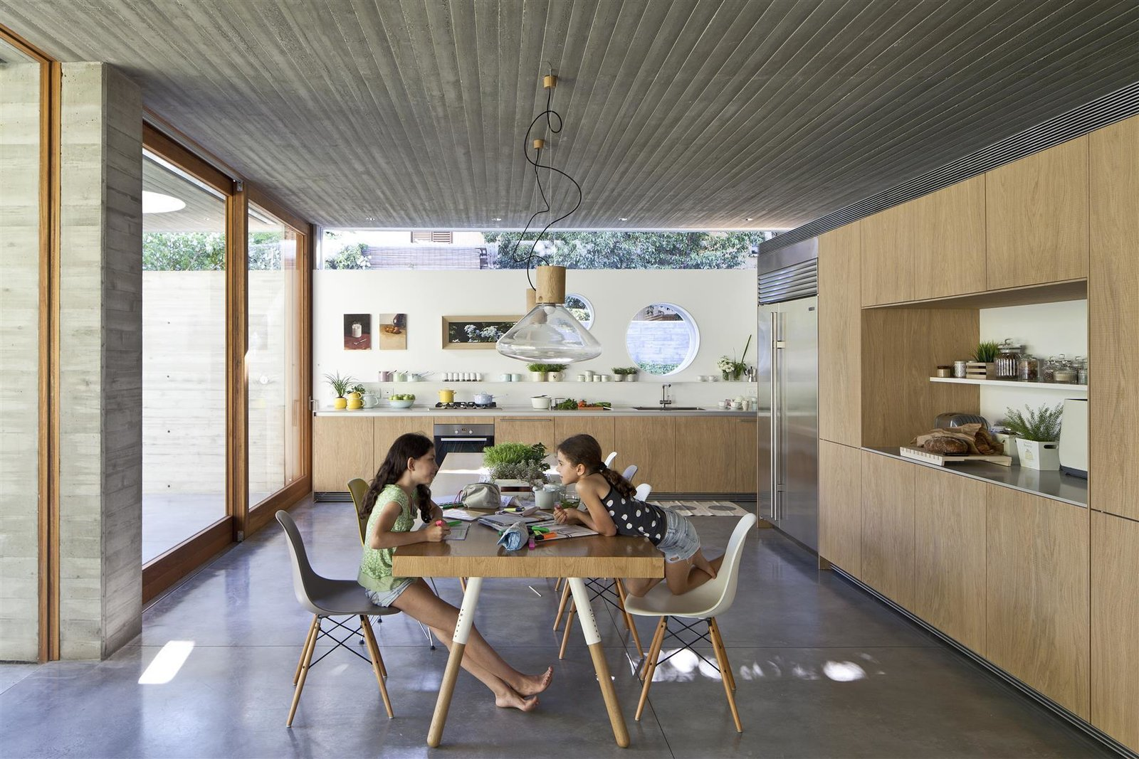 Kitchen, Wood, Concrete, Ceiling, Refrigerator, Dishwasher, Range, Cooktops, Drop In, and Open  Best Kitchen Concrete Refrigerator Wood Ceiling Drop In Cooktops Photos from An Architect's Bright and Airy Family Home Thrives Within a Brutalist Concrete Structure