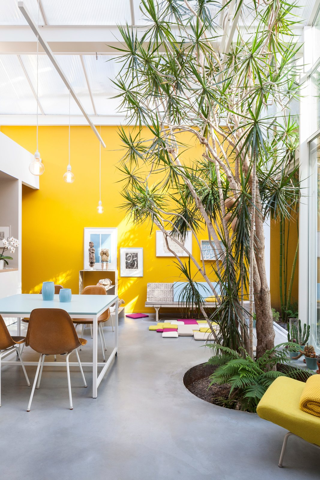 A cozy kitchen-dinning area in the studio and home of an Antwerp artist couple with Eames chairs, a second hand sofa and mustard-yellow walls.  Photo 10 of 10 in 9 Small Spaces With  Color
