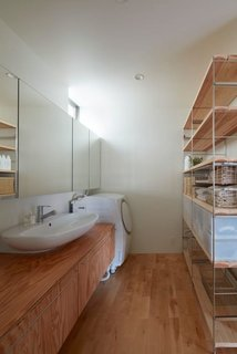 In a Japanese home designed by Koizumisekkei, mirrors and a slim shelf made of raw wood and metal line one side of the wall, creating the illusion of expansiveness in the laundry room.