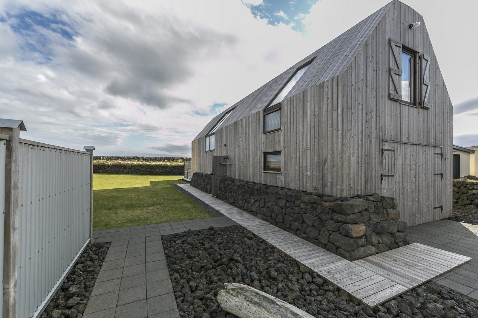 Outdoor, Side Yard, Grass, Walkways, Wood, Hardscapes, Concrete, Vertical, and Metal  Outdoor Side Yard Concrete Wood Metal Photos from Get in Touch With Iceland's Rugged Landscape While Staying at This Modern Coastal Barn