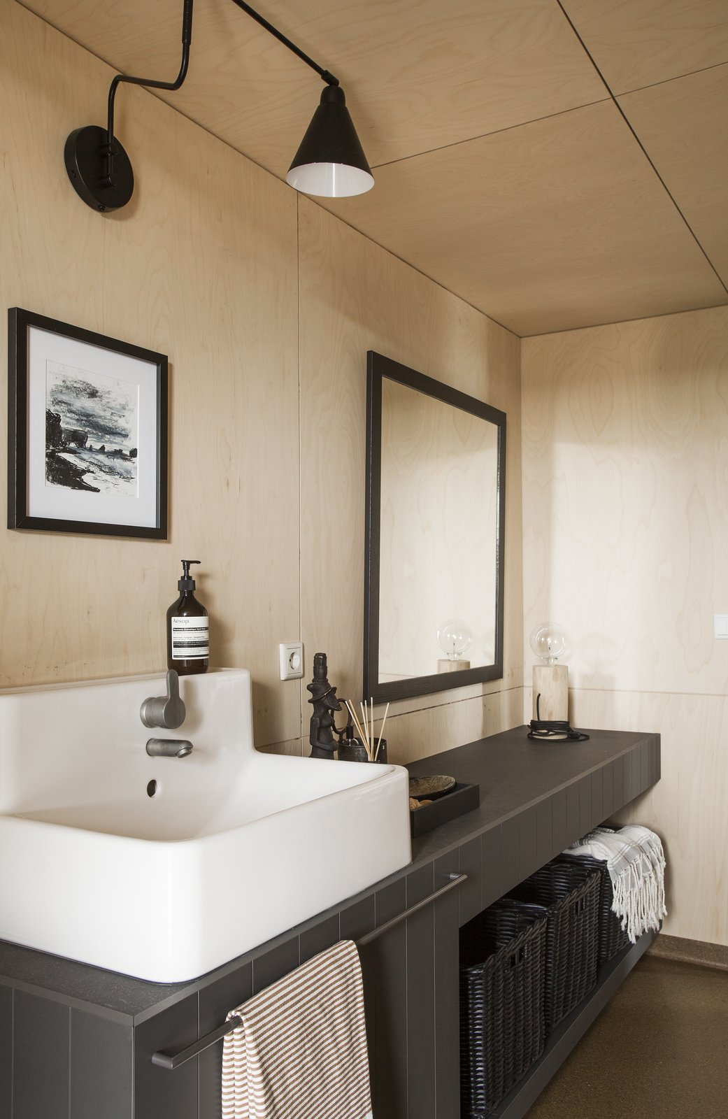 Bath Room, Tile Counter, Vessel Sink, Wall Lighting, and Table Lighting  Photo 9 of 12 in Get in Touch With Iceland's Rugged Landscape While Staying at This Modern Coastal Barn