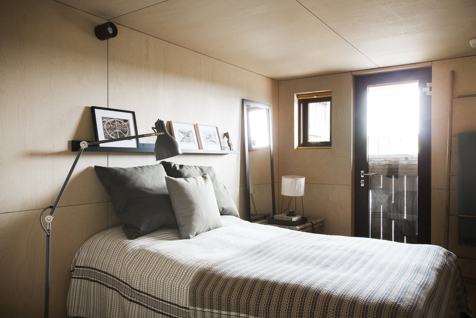 Bedroom, Bed, Floor Lighting, Table Lighting, Night Stands, Light Hardwood Floor, Wall Lighting, and Shelves  Photo 12 of 12 in Get in Touch With Iceland's Rugged Landscape While Staying at This Modern Coastal Barn