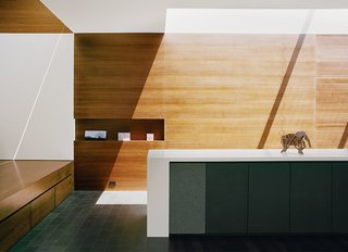 This San Francisco renovation by architect Cary Bernstein is designed with a streamlined built-in cabinet system with built-in speakers, niches for artwork, and drawers tucked under the entryway mezzanine.