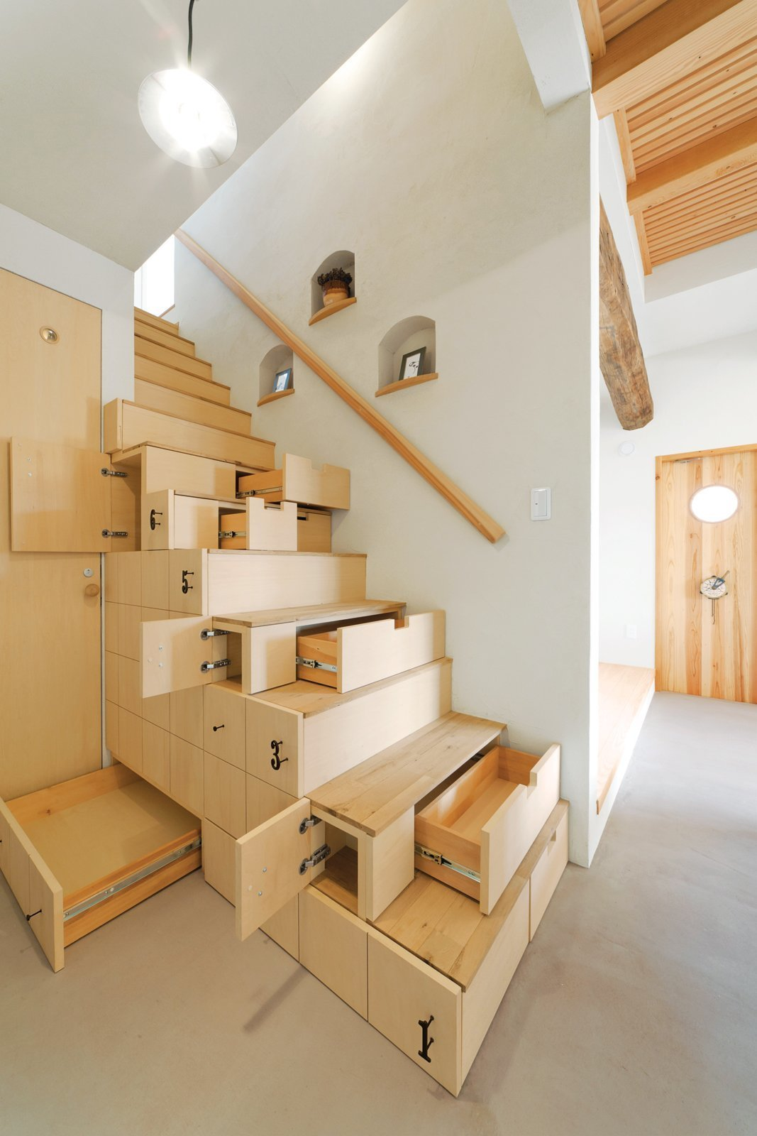 """Using a centuries-old Japanese carpentry concept of """"kaidan dansu"""" – mobile storage cabinetry, this home in Koriyama, Japan by architect Kotaro Anzai has a modern staircase cabinet made of linden plywood that connects the ground floor living room to the upper level of the house.  Photo 5 of 10 in 10 Homes With Clever Storage Solutions"""