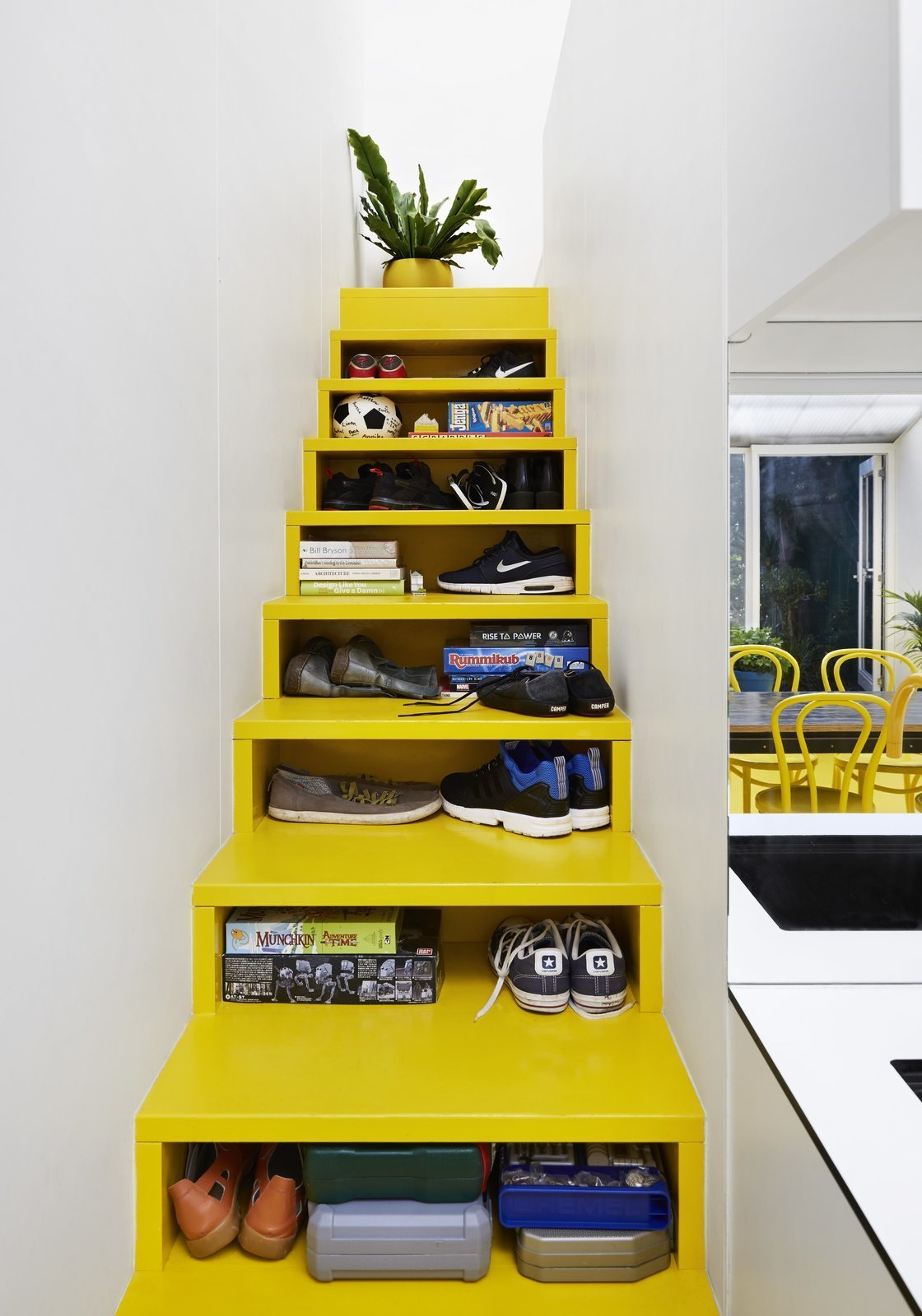 Architect Andrew Maynard's Melbourne home, which also doubles up as the office of his practice Austin Maynard Architects, includes a bright yellow staircase with opening slots in the front that serve as shelving and storage space.  Photo 9 of 10 in 10 Homes With Clever Storage Solutions