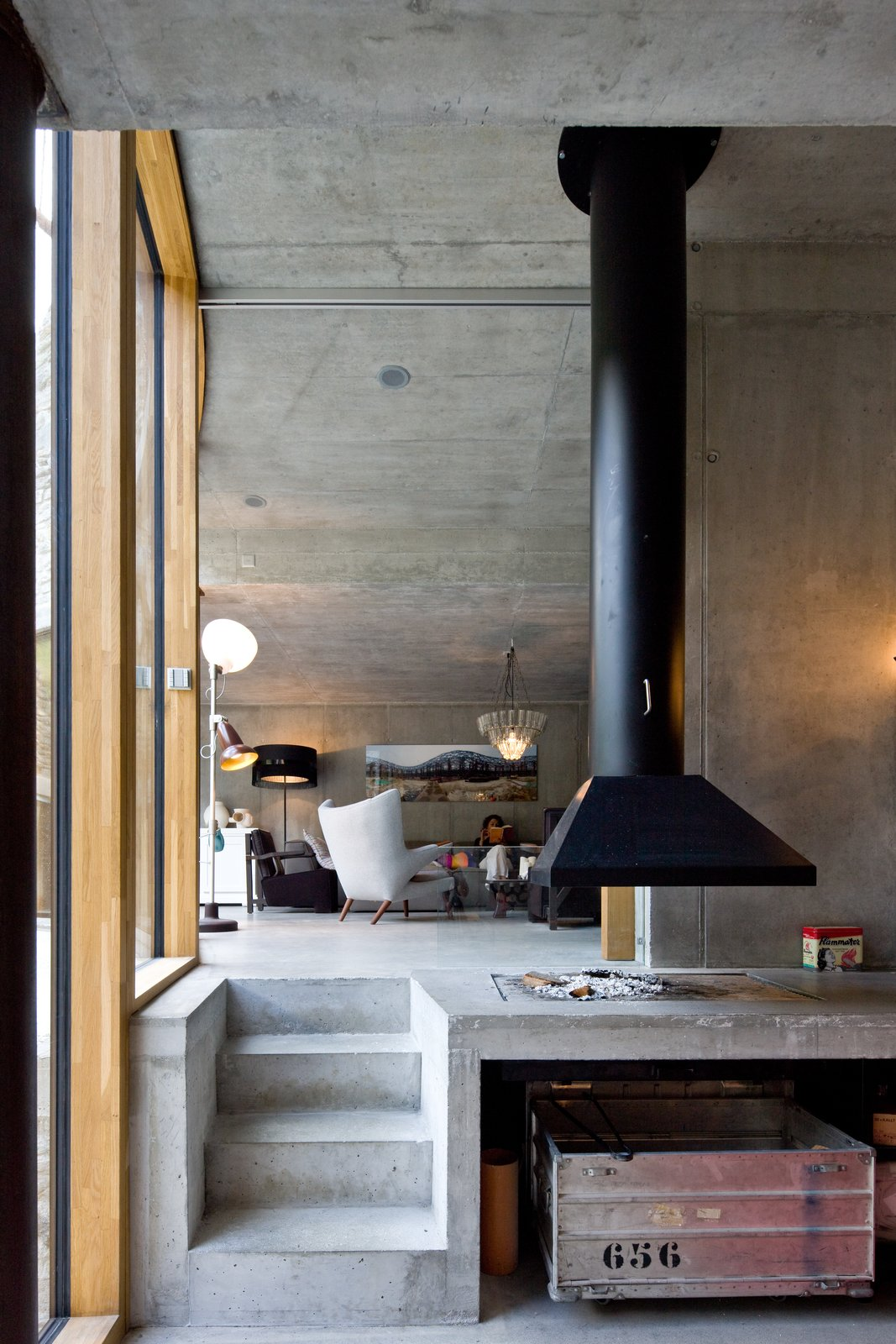 Living Room, Hanging Fireplace, Concrete Floor, Chair, Pendant Lighting, and Floor Lighting  Photo 3 of 13 in Stay in a Swiss Vacation Home That's Literally Inside a Mountain