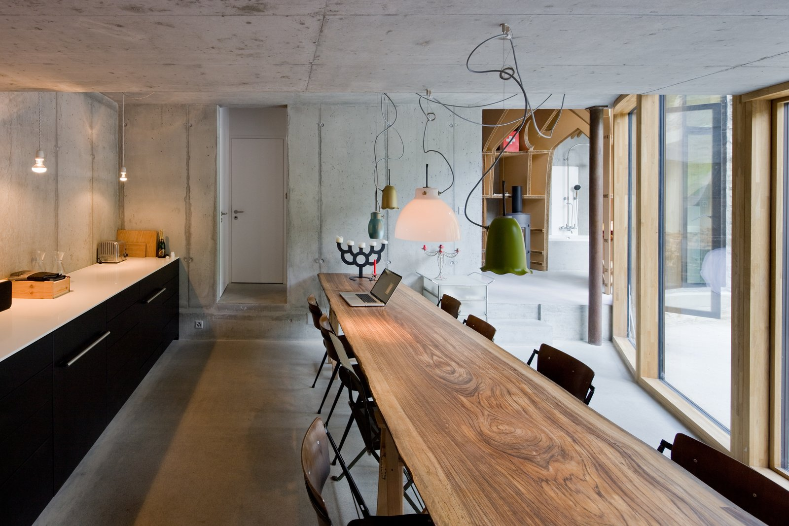 Dining Room, Chair, Pendant Lighting, Table, Concrete Floor, and Storage  Photos from Stay in a Swiss Vacation Home That's Literally Inside a Mountain