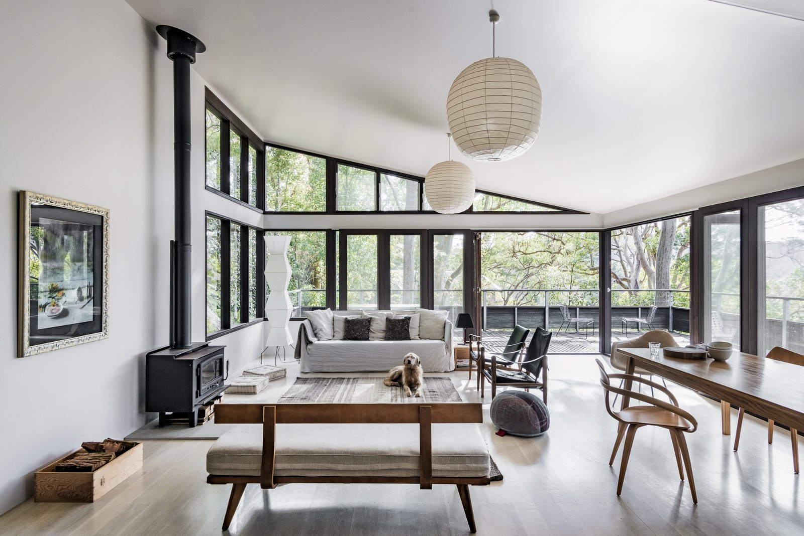 Living Room, Chair, Pendant Lighting, Sofa, Wood Burning Fireplace, Light Hardwood Floor, and Ottomans  Photo 2 of 13 in Stay in a Riverside Vacation Home That Embraces the Australian Bush