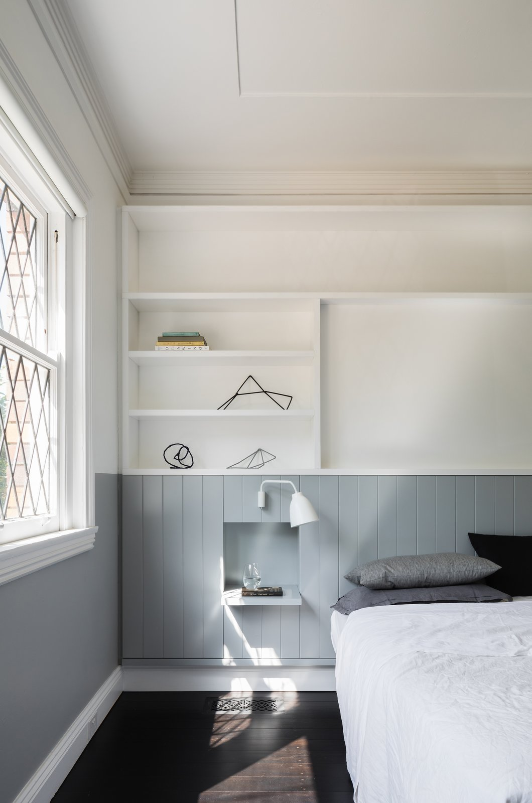 Bedroom, Shelves, Wall Lighting, Bed, and Dark Hardwood Floor  Photo 10 of 13 in This 1930s Bungalow in Sydney Was Preserved in the Front and Updated in the Back
