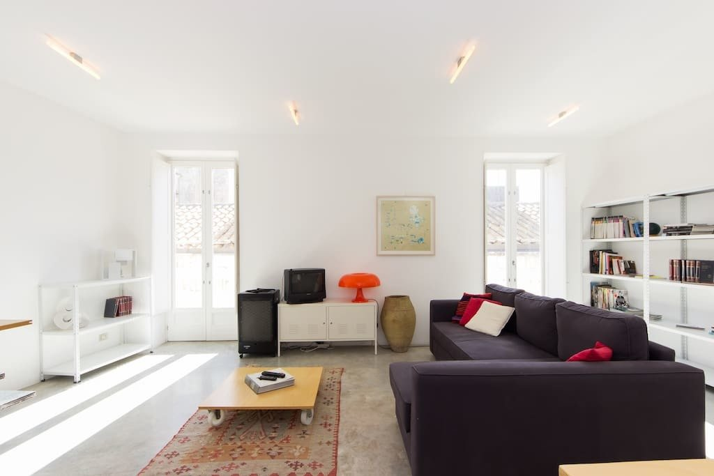 Living Room, Coffee Tables, Storage, Ceiling Lighting, Accent Lighting, Concrete Floor, Shelves, Rug Floor, and Sectional  Photo 7 of 9 in You Can Rent This Small Sicilian Apartment For $94 a Night