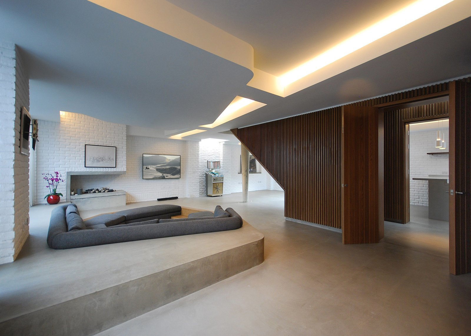 Living Room, Concrete Floor, Sectional, Wood Burning Fireplace, Corner Fireplace, and Accent Lighting On a site surrounded by Victorian homes in Primrose Hill, Patalab Architecture transformed a former mechanic's garage into a three-bedroom house and two one-bedroom apartments.  Photo 6 of 9 in 8 Stylish London Apartments