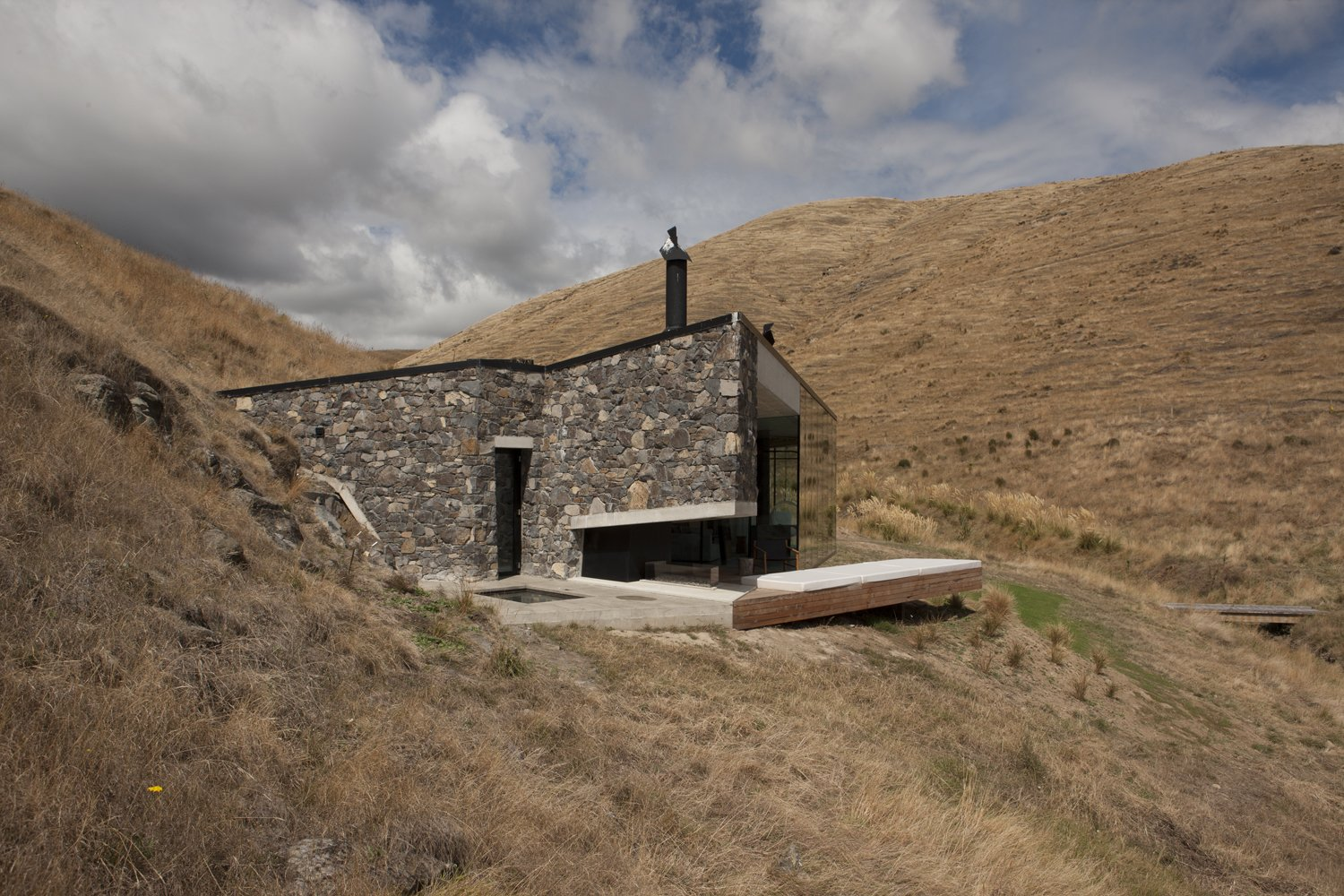 Tagged: Exterior, House, Glass Siding Material, Cabin Building Type, and Stone Siding Material.  Photo 2 of 10 in Stay at a Stone-and-Glass Retreat in a Remote New Zealand Bay
