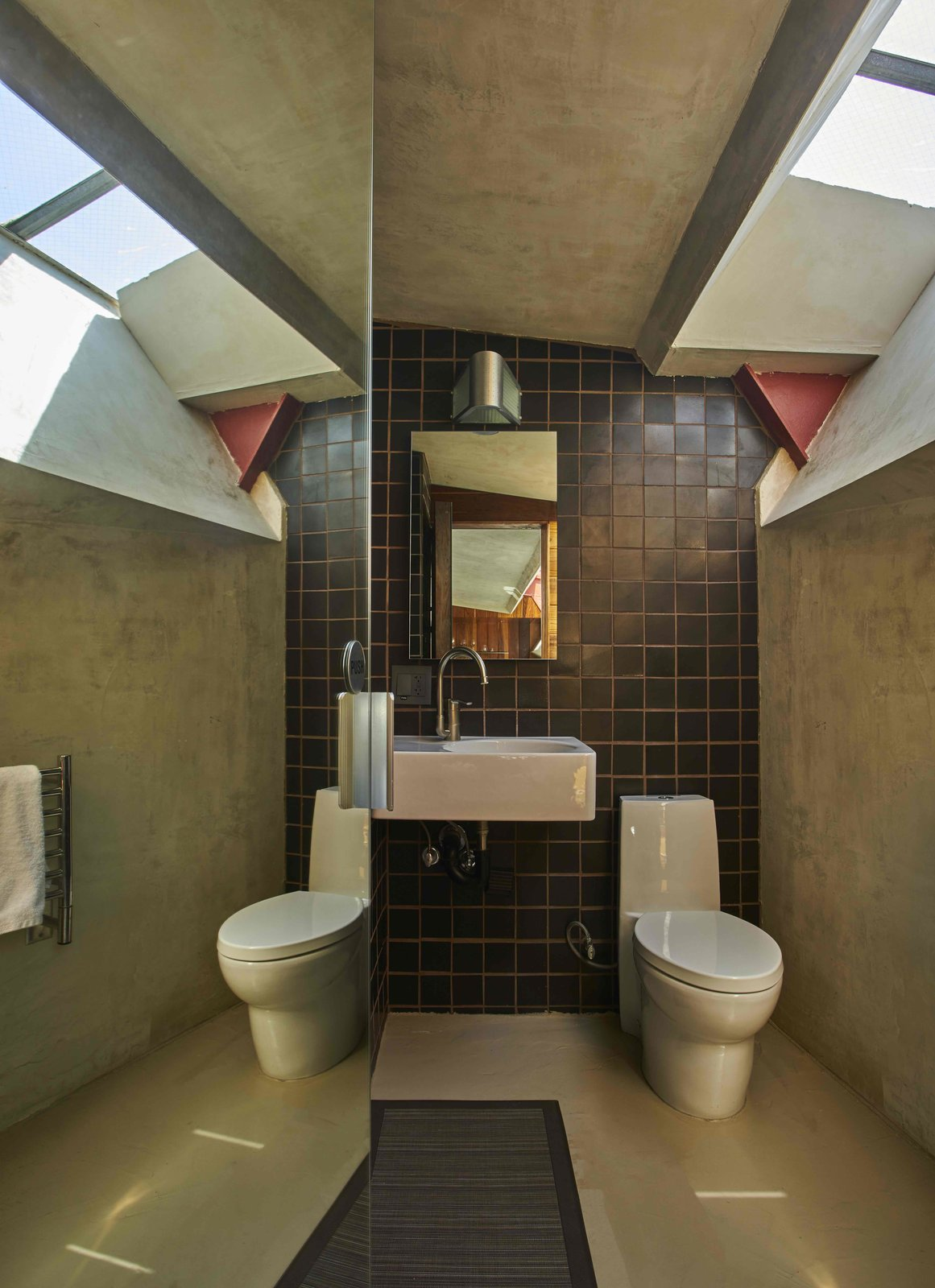 Bath Room, Ceramic Tile Wall, Wall Lighting, Wall Mount Sink, Two Piece Toilet, and Concrete Floor  The Lautner from Escape to a John Lautner Micro-Resort in the Californian Desert