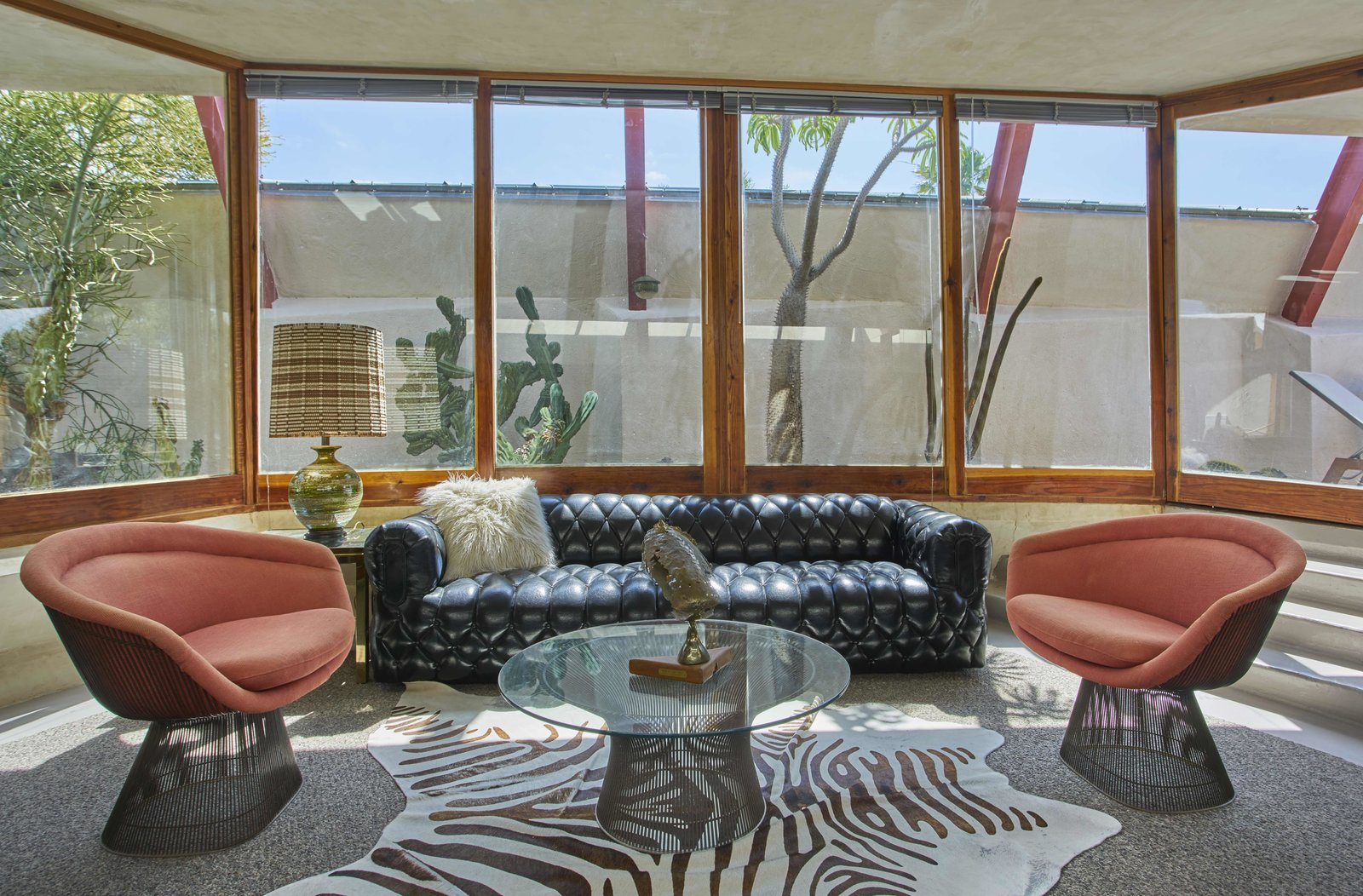 Living Room, Sofa, Lamps, Chair, Coffee Tables, End Tables, Rug Floor, Carpet Floor, Concrete Floor, and Table Lighting  Photo 12 of 13 in Escape to a John Lautner Micro-Resort in the Californian Desert