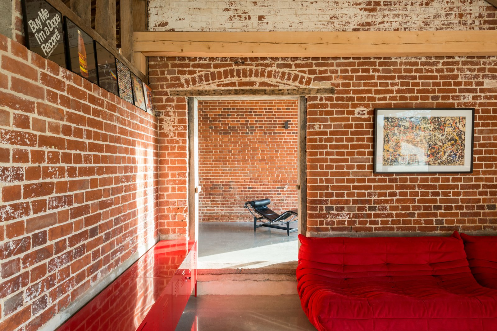 Living Room, Sectional, Chair, and Concrete Floor  Photo 9 of 10 in A Suffolk Barn Home With Soaring Ceilings Listed at $1.95M