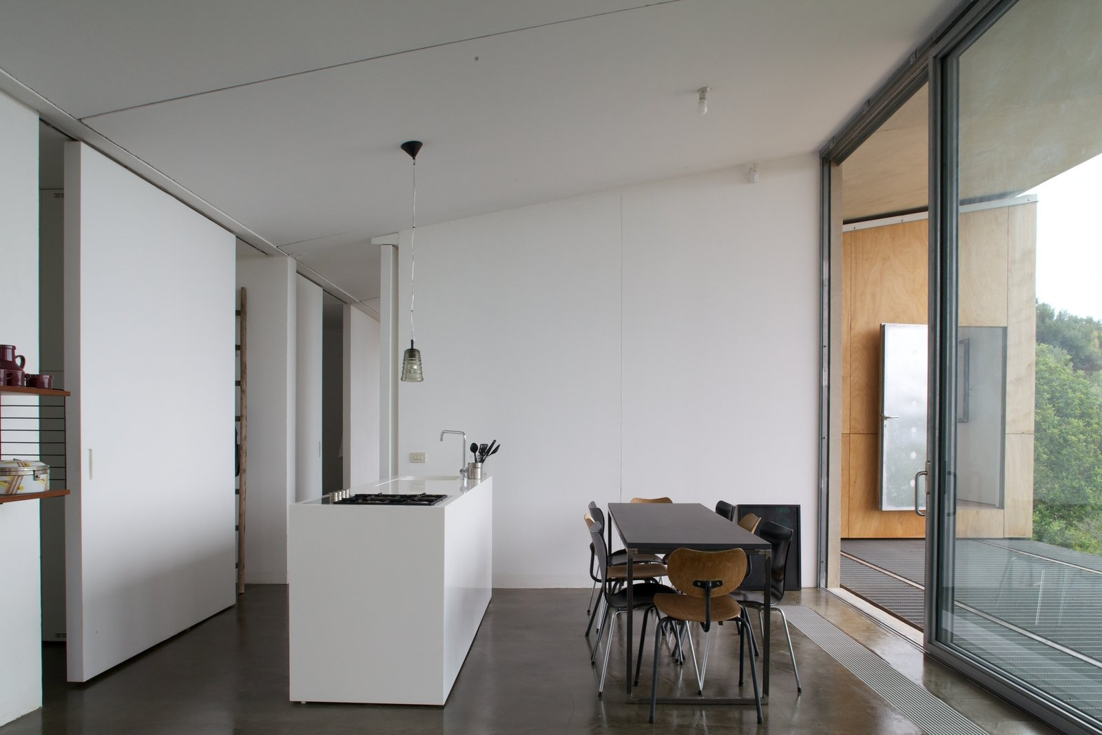 Kitchen, White Cabinet, Concrete Floor, Pendant Lighting, Cooktops, and Drop In Sink  Photo 7 of 12 in Stay in a Minimalist Villa in the Sicilian Countryside, Complete With Sea Views