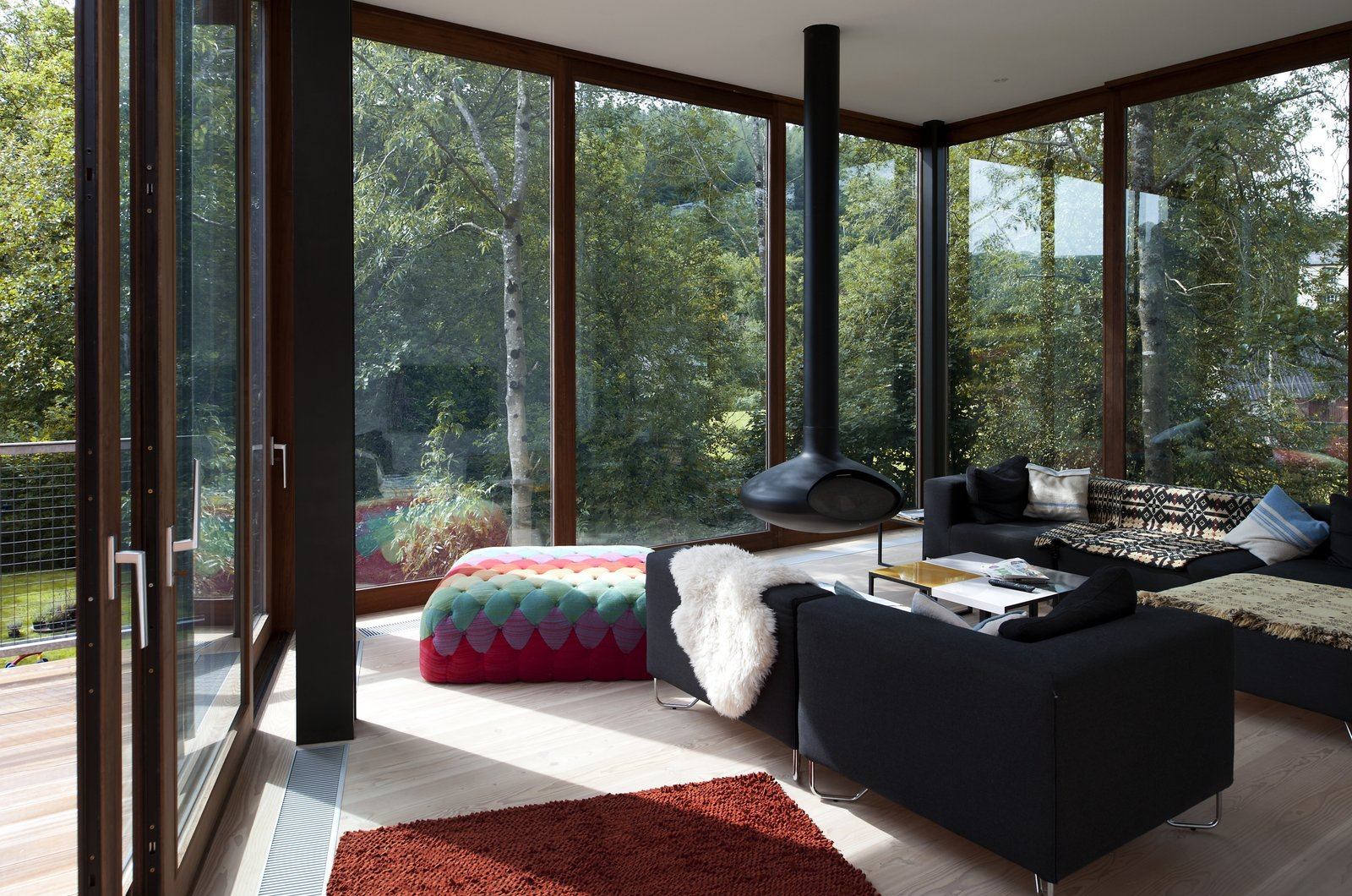 Living Room, Sofa, Hanging Fireplace, Ottomans, and Light Hardwood Floor  Ty Hedfan from A Hovering House in the Welsh Hills That You Can Call Your Own For a Week