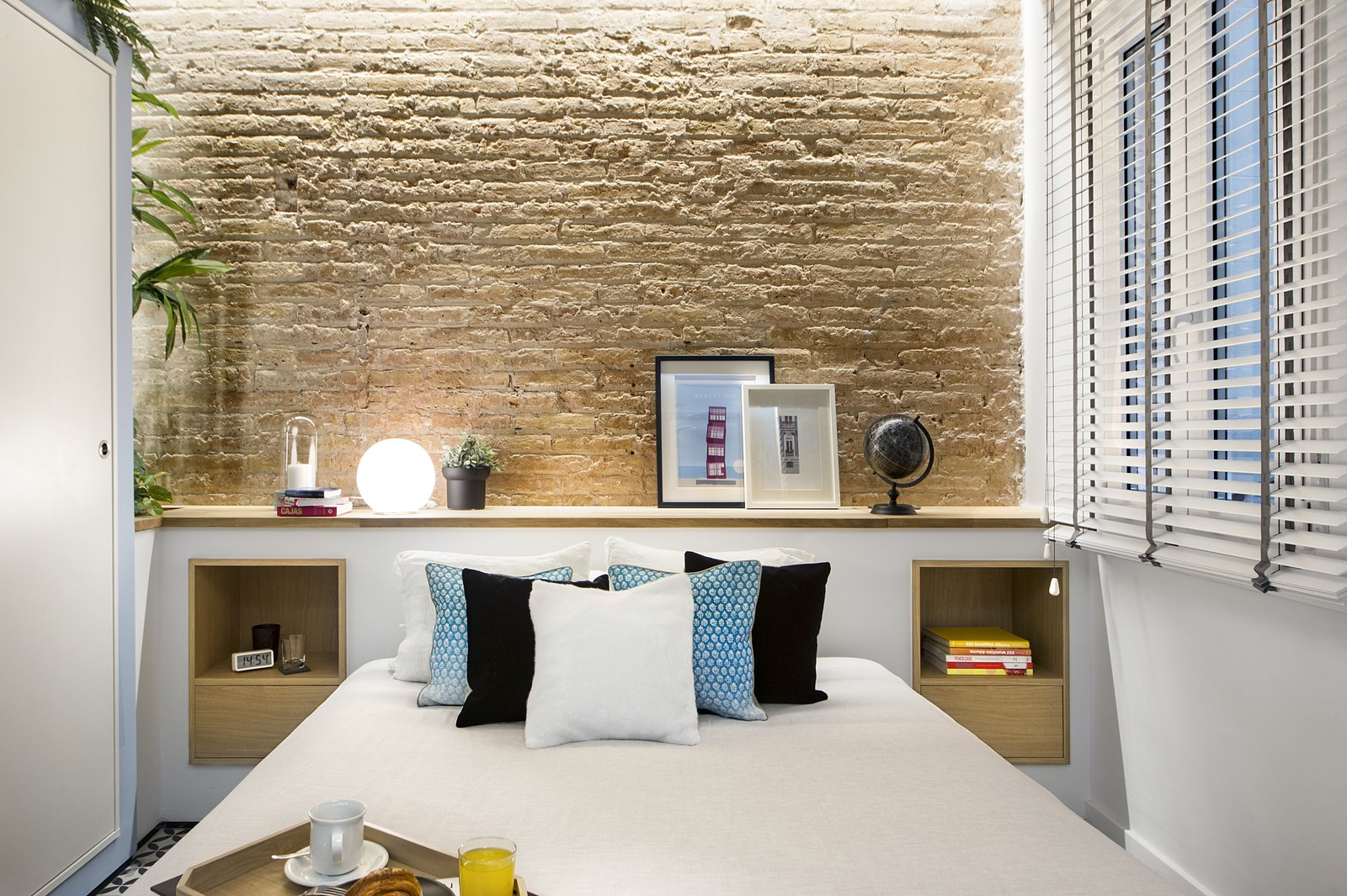Bedroom, Shelves, Table Lighting, Bed, and Porcelain Tile Floor  Urban Beach Home from A Smart Layout Maximizes Space in This Compact Urban Beach Apartment in Barcelona