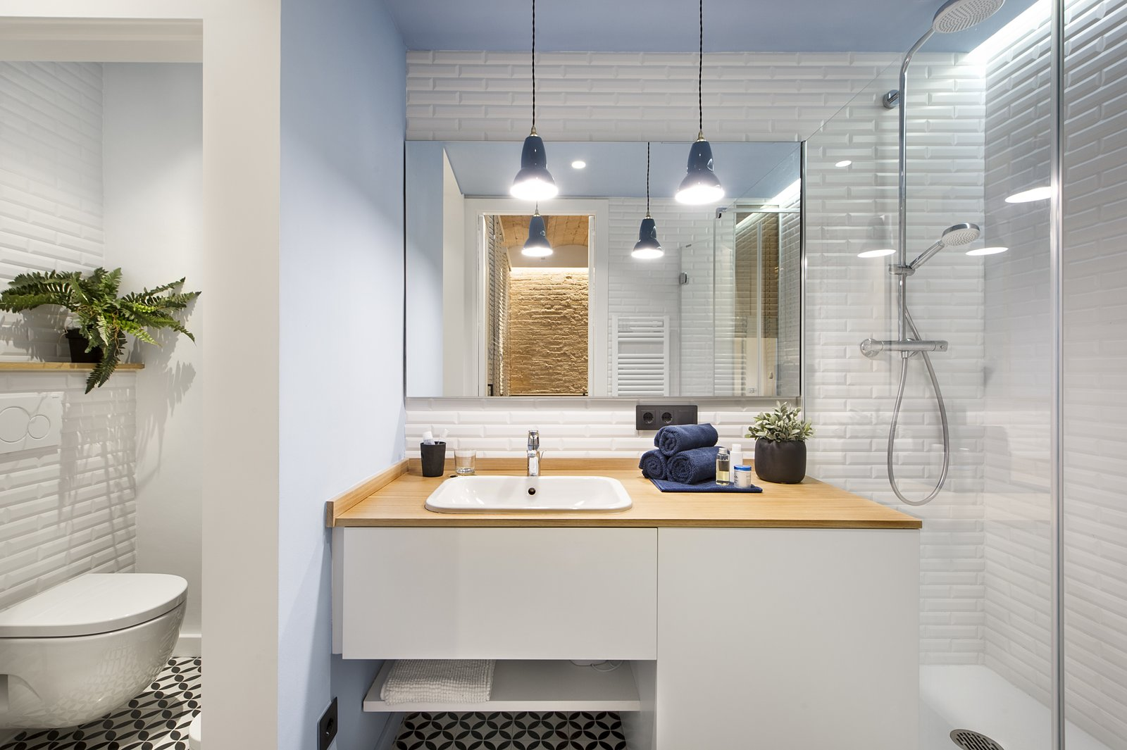 Bath Room, Wood Counter, Pendant Lighting, Enclosed Shower, One Piece Toilet, Drop In Sink, Ceramic Tile Wall, and Ceramic Tile Floor  Photo 8 of 11 in A Smart Layout Maximizes Space in This Compact Urban Beach Apartment in Barcelona