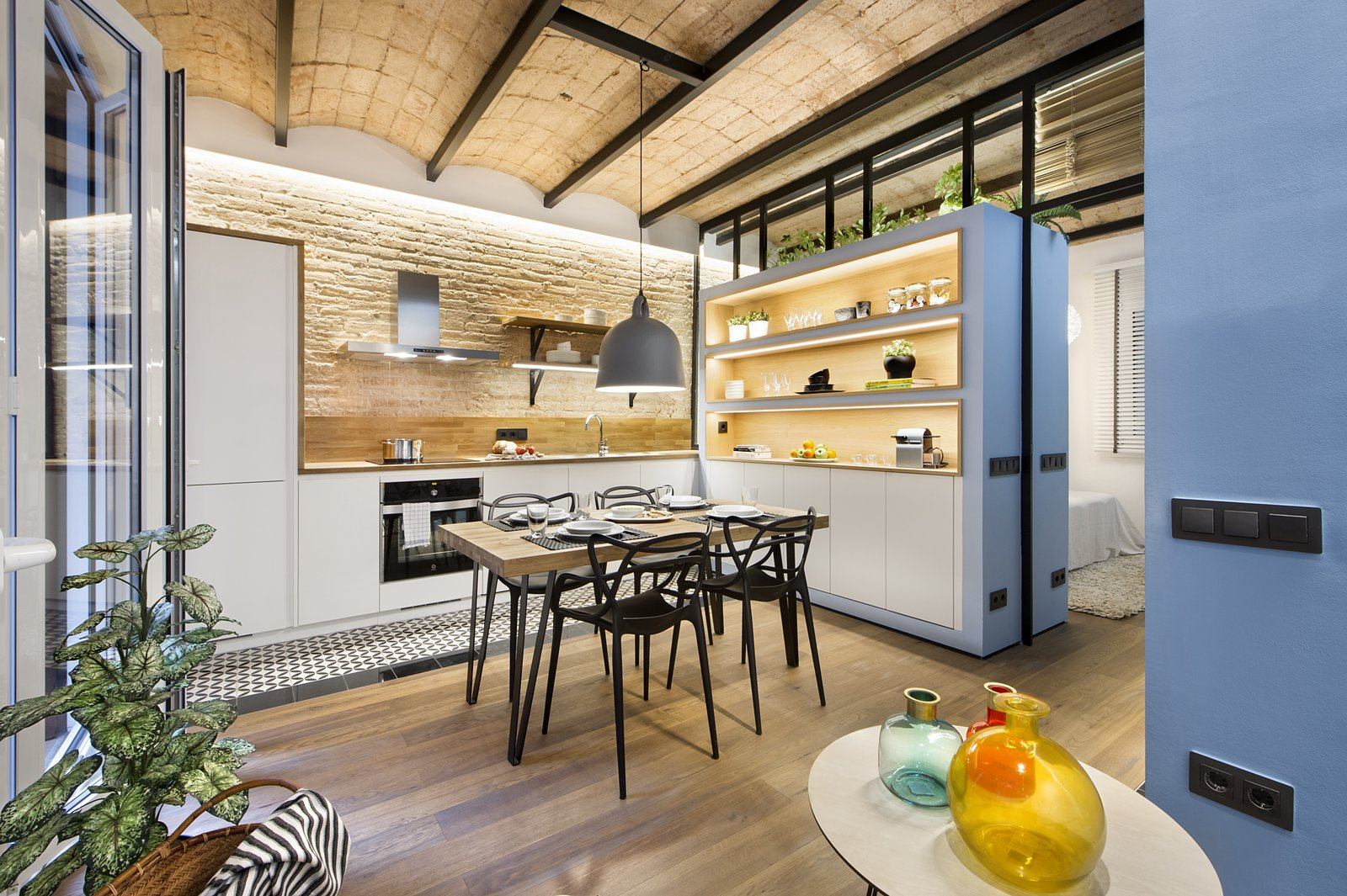 Kitchen, Wood Counter, Light Hardwood Floor, Pendant Lighting, Wood Backsplashe, Wall Oven, Ceiling Lighting, Range Hood, Range, Drop In Sink, and Ceramic Tile Floor  Urban Beach Home from A Smart Layout Maximizes Space in This Compact Urban Beach Apartment in Barcelona