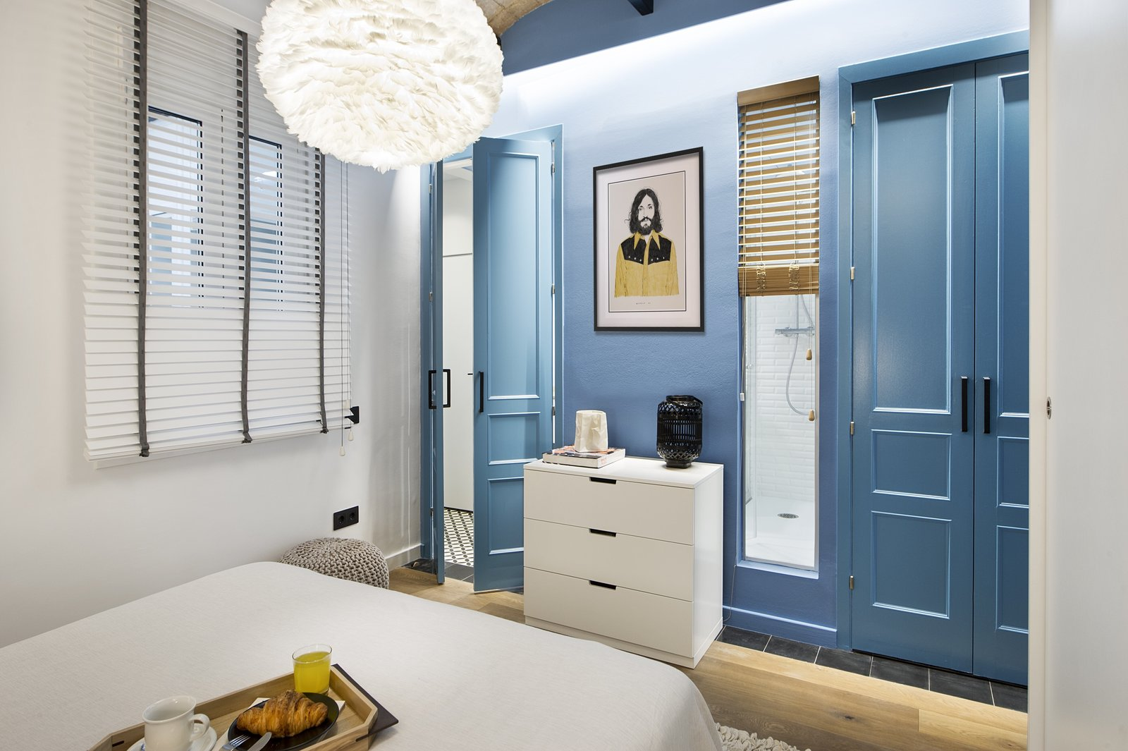 Bedroom, Dresser, Pendant Lighting, Light Hardwood Floor, and Bed  Photo 2 of 11 in A Smart Layout Maximizes Space in This Compact Urban Beach Apartment in Barcelona