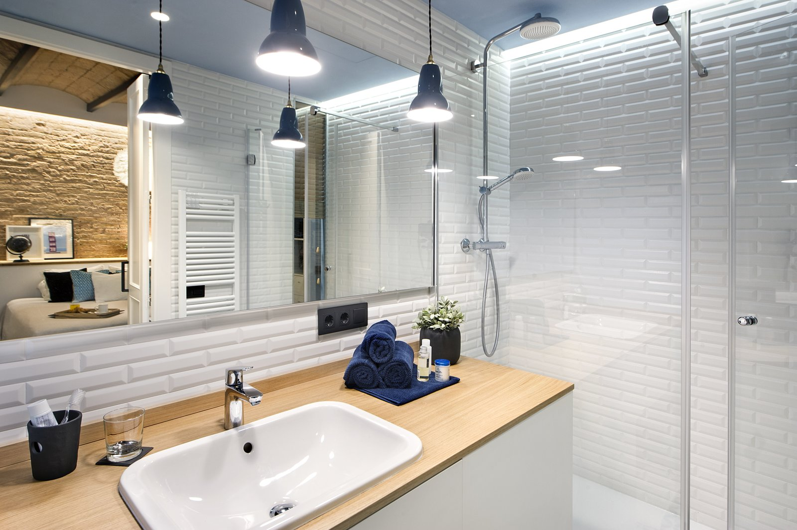 Bath Room, Wood Counter, Enclosed Shower, Drop In Sink, Pendant Lighting, and Ceramic Tile Wall  Photo 10 of 11 in A Smart Layout Maximizes Space in This Compact Urban Beach Apartment in Barcelona