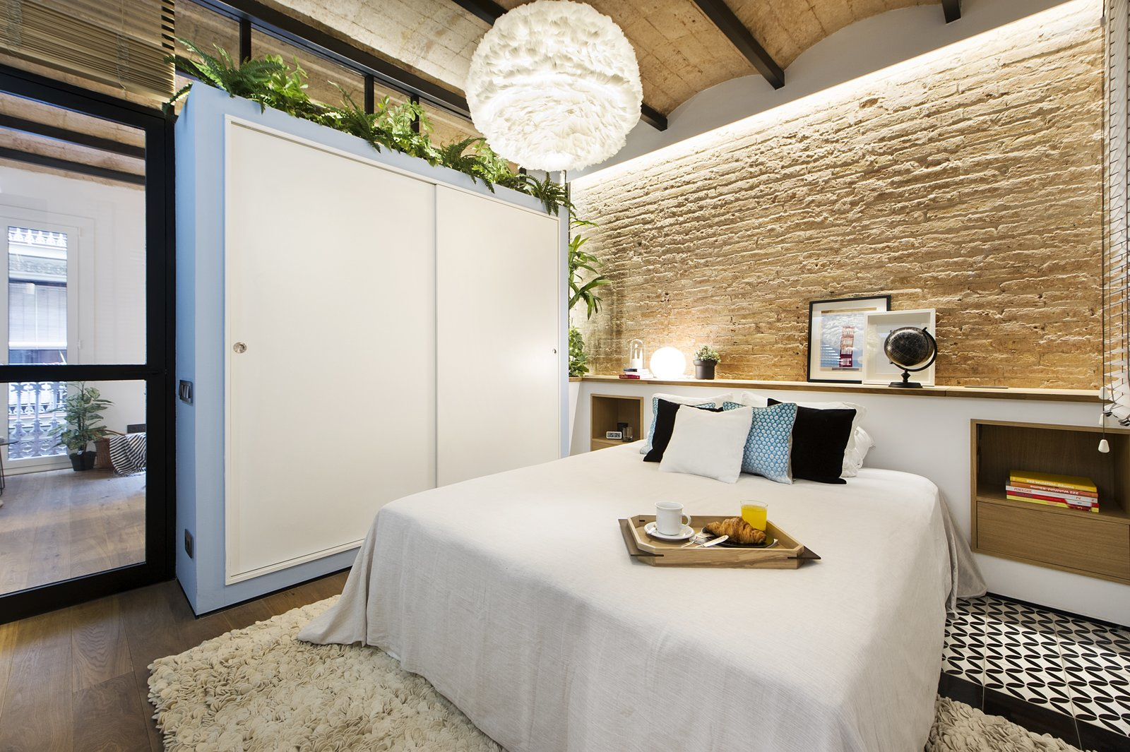 Bedroom, Table Lighting, Bed, Storage, Pendant Lighting, Medium Hardwood Floor, and Ceramic Tile Floor  Photo 6 of 11 in A Smart Layout Maximizes Space in This Compact Urban Beach Apartment in Barcelona