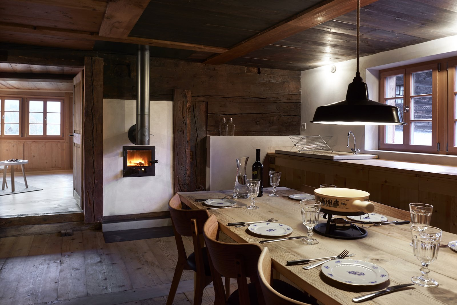 Dining Room, Wood Burning Fireplace, Dark Hardwood Floor, Chair, Table, and Pendant Lighting  Photo 3 of 13 in A Renovated Pagan House in the Swiss Alps Puts Guests in Touch With the Past