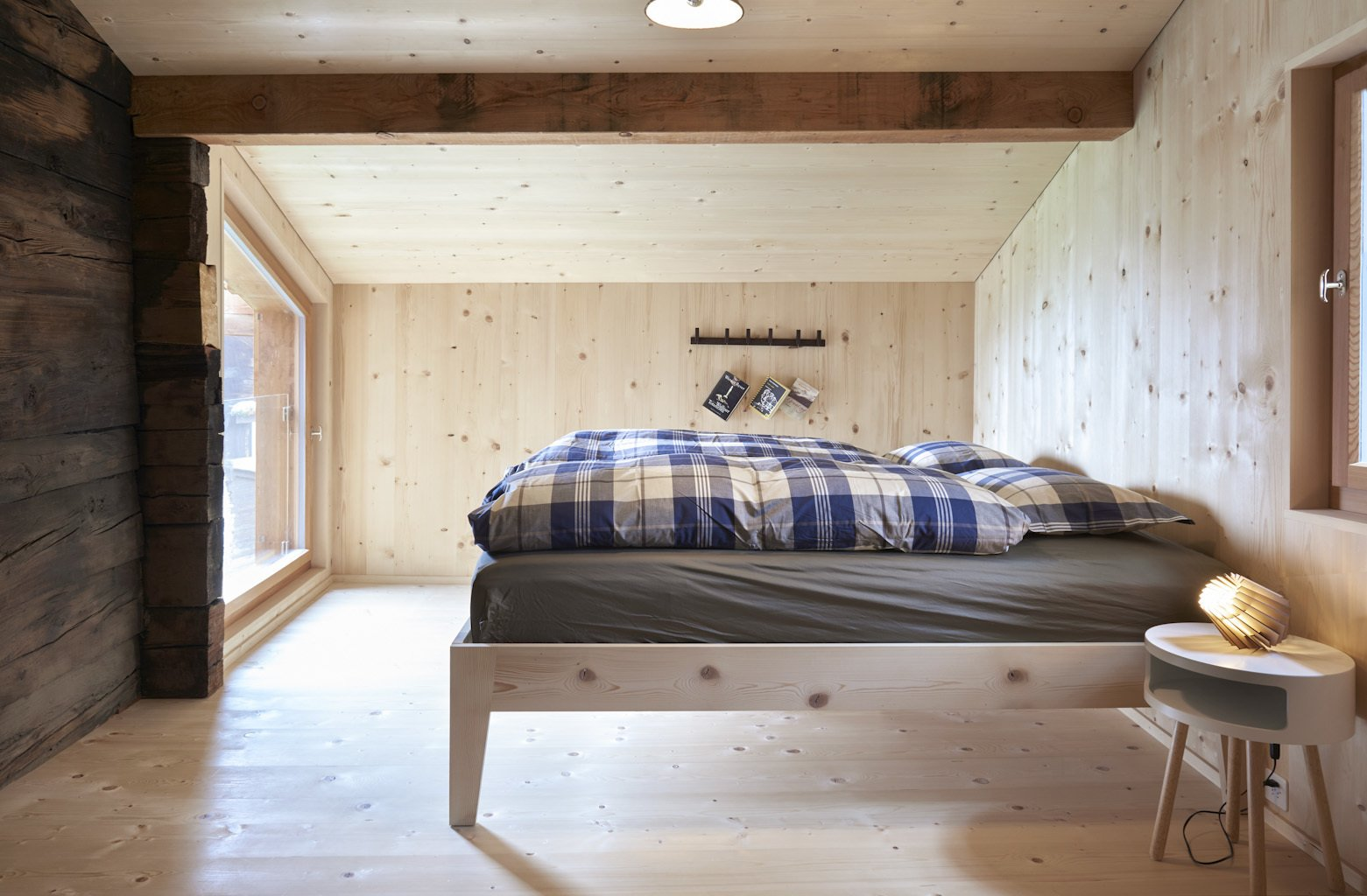 Bedroom, Bed, Night Stands, Light Hardwood Floor, and Table Lighting  Photo 5 of 13 in A Renovated Pagan House in the Swiss Alps Puts Guests in Touch With the Past