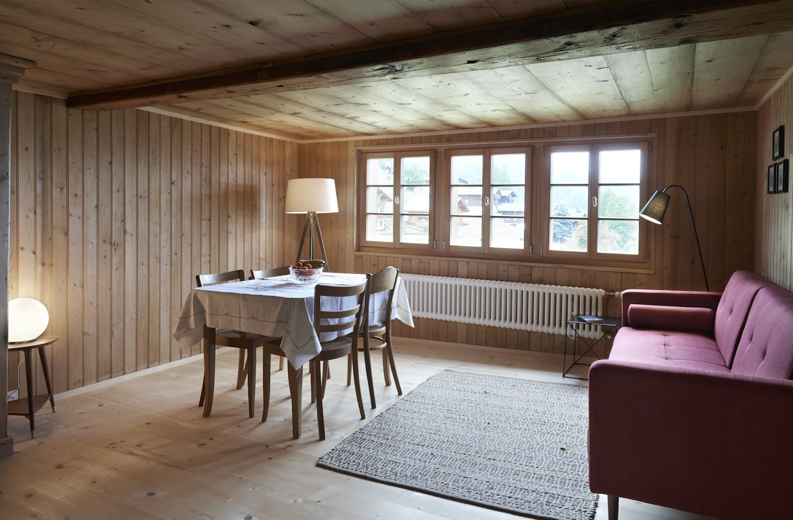Living Room, Sofa, Floor Lighting, Chair, Table, and Light Hardwood Floor  Photo 6 of 13 in A Renovated Pagan House in the Swiss Alps Puts Guests in Touch With the Past