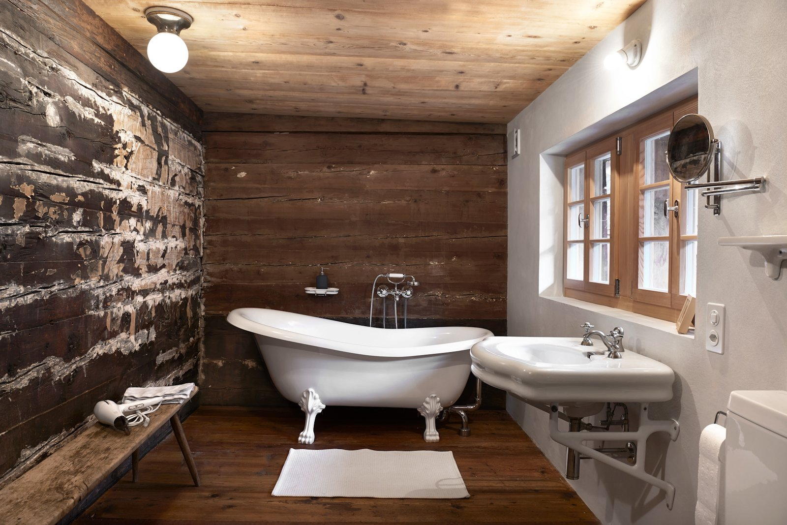 Bath Room, Freestanding Tub, Wall Mount Sink, and Dark Hardwood Floor  Photo 12 of 13 in A Renovated Pagan House in the Swiss Alps Puts Guests in Touch With the Past
