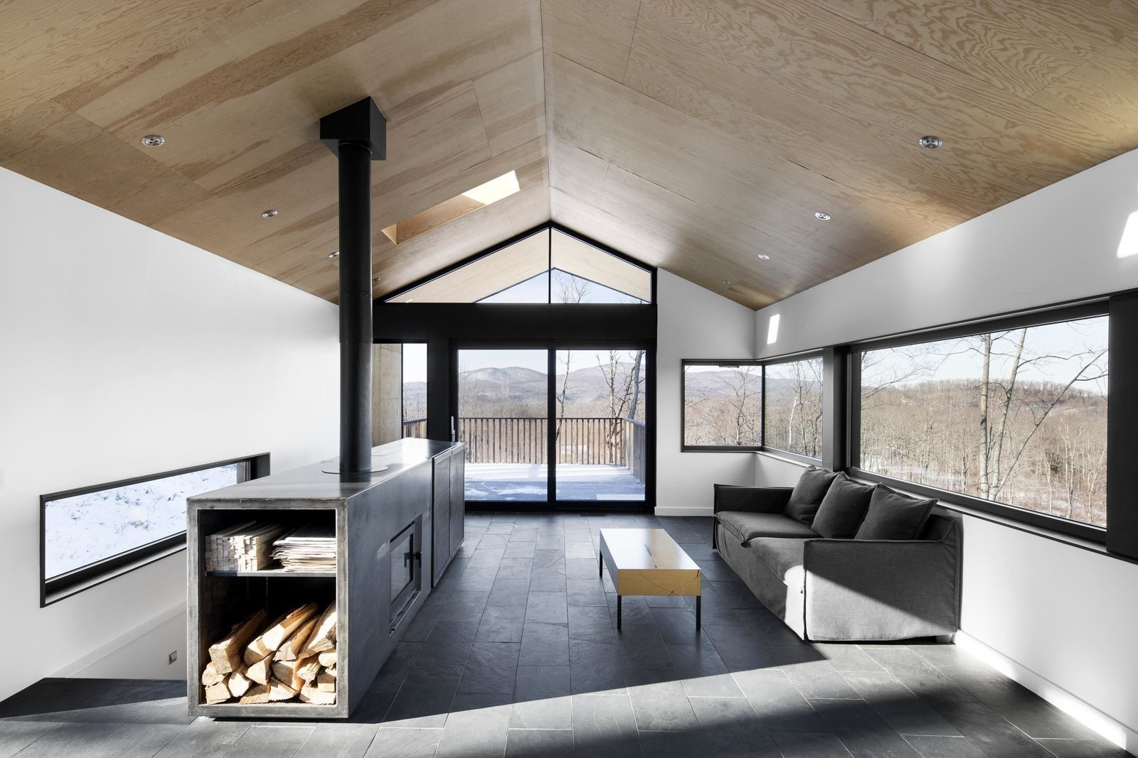 Living Room, Standard Layout Fireplace, Coffee Tables, Sofa, Slate Floor, Wood Burning Fireplace, and Recessed Lighting This home in the snowy forests of Eastern Quebec, a centralized fireplace was built into a custom, multi-purpose cabinet welded from sheets of hot-rolled steel.  Photo 9 of 10 in 10 Modern Fireplaces That Make For Inviting Interiors