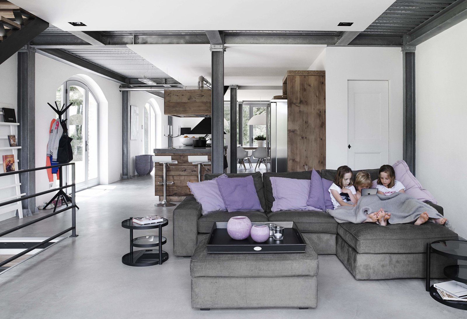 Living Room, Stools, Recessed Lighting, Sectional, Bar, Concrete Floor, Ottomans, and End Tables  Photo 1 of 11 in Stay in a Modern, Industrial Home That's Hidden Inside a Traditional Tuscan Villa