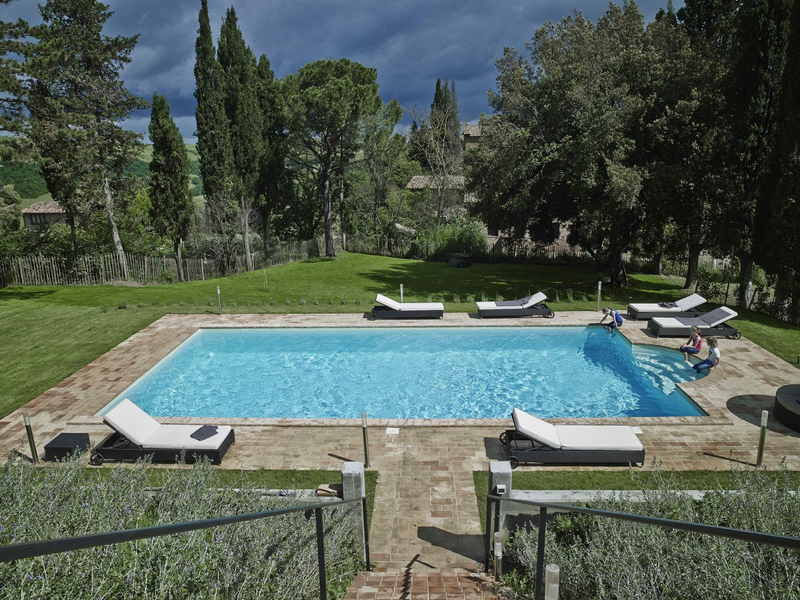 Outdoor, Back Yard, Grass, Swimming Pools, Tubs, Shower, Large Pools, Tubs, Shower, Vertical Fences, Wall, and Trees  Photo 3 of 11 in Stay in a Modern, Industrial Home That's Hidden Inside a Traditional Tuscan Villa