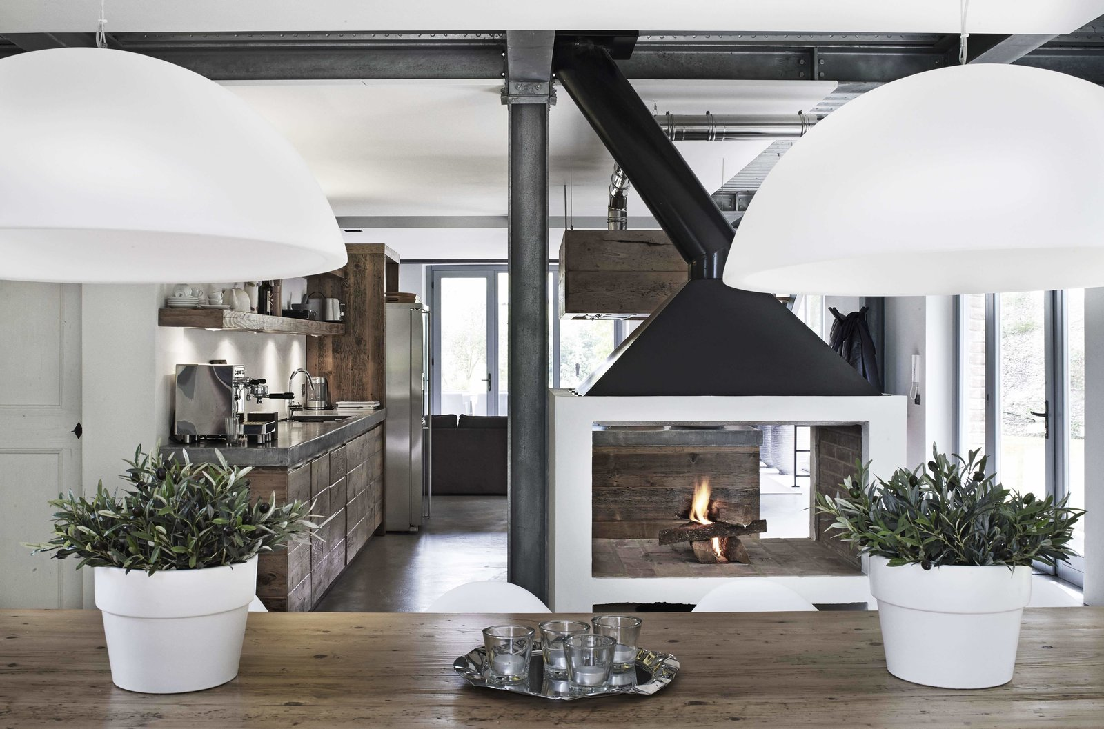 Dining Room, Pendant Lighting, Standard Layout Fireplace, Two-Sided Fireplace, Dark Hardwood Floor, Wood Burning Fireplace, and Table  Photo 4 of 11 in Stay in a Modern, Industrial Home That's Hidden Inside a Traditional Tuscan Villa