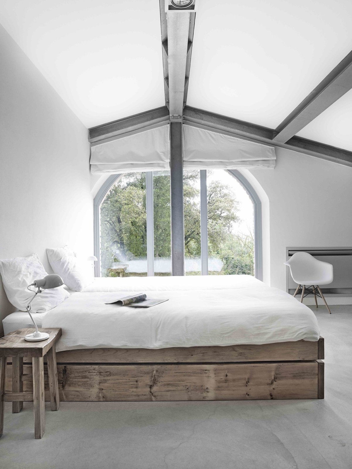 Bedroom, Chair, Night Stands, Concrete Floor, Bed, Table Lighting, and Lamps  Photo 6 of 11 in Stay in a Modern, Industrial Home That's Hidden Inside a Traditional Tuscan Villa